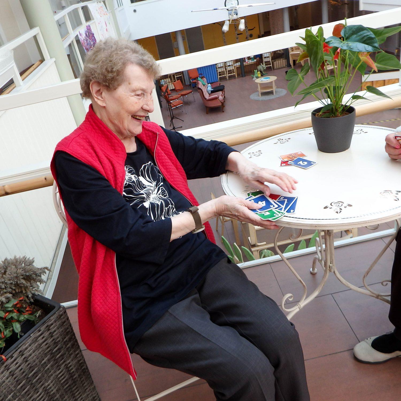 Raija pöydän ääressä sekoittamassa skipbo-kortteja